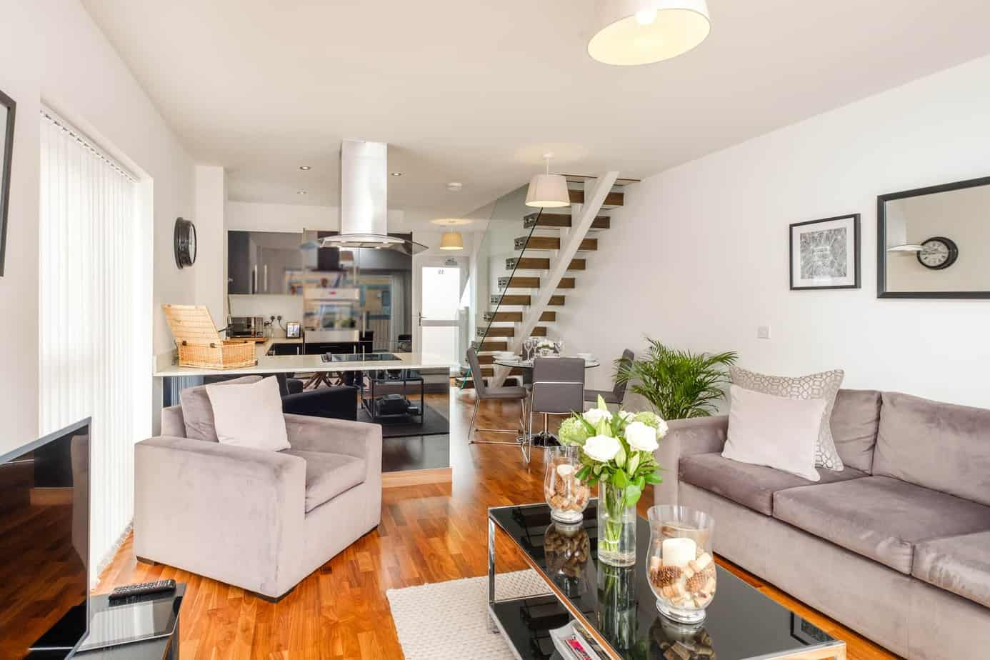 Grand Central Serviced Apartment Cambridge Tailored Stays livingroom with grey sofa and kitchen in the background