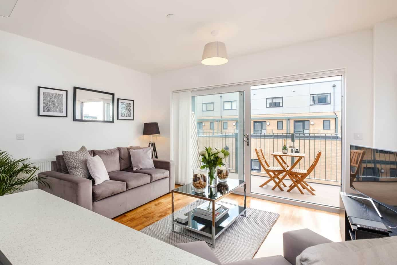 Grand Central Serviced Apartment Cambridge Tailored Stays livingroom with grey sofa and  balcony
